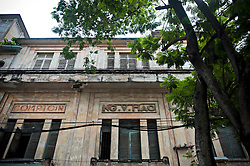 Old frontage of a french colonial buidling in district 1, Ho Chi Minh city, Vietnam, Asia. Some french and vietnamese writes are painted and graved on the walls.