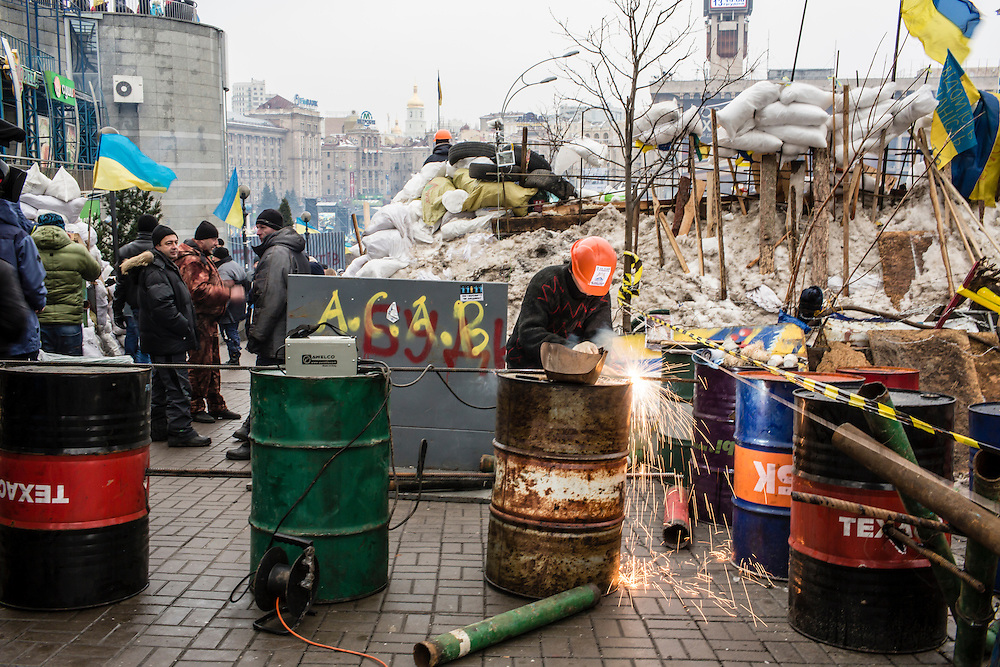 KIEV, UKRAINE - DECEMBER 13: A man welds rebar to oil drums to create barriers used to keep the police from forcing anti-government protesters out of Independence Square on December 13, 2013 in Kiev, Ukraine. Thousands of people have been protesting against the government since a decision by Ukrainian president Viktor Yanukovych to suspend a trade and partnership agreement with the European Union in favor of incentives from Russia. (Photo by Brendan Hoffman/Getty Images) *** Local Caption ***