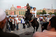 Kashgar: A tourist has his picture taken whilst riding a horse on the Id Khar Mosque square...Despite the migration of millions of Han Chinese to the western part of the Xinjiang Uighur Autonomous Region, the Uighur community continue to practice their muslim culture and resist the suppression of their cultural and religious traditions by the Chinese government....The chinese government has been criticised for the redevelopment of the old city, which has involved the destruction of many of the old houses in the town that were built without regulation, officials claiming them to be overcrowded and uncompliant with earthquake codes...Many in the chinese government believe Kashgar to a breeding ground for Uighur separatists, who Beijing claim to have links to terrorism...The european parliament has called for a halt to the cultural destruction of Kashgar, suggesting that Kashgar be added tot he UNESCO World heritage 'Silk Road' project, and calling on the chinese government to develop a genuine Han-Uighur dialogue to adopt more inclusive and comprehensive economic policies in Xinjiang in order to protect the cultural identity of the Uighur population..©JTanner/July 2011