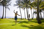 A young couple slacklining between palm trees in Poipu, Kauai.