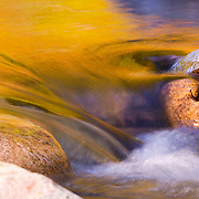 Vibrant fall colors reflect on the Swift River, which flows through the White Mountains in New Hampshire..