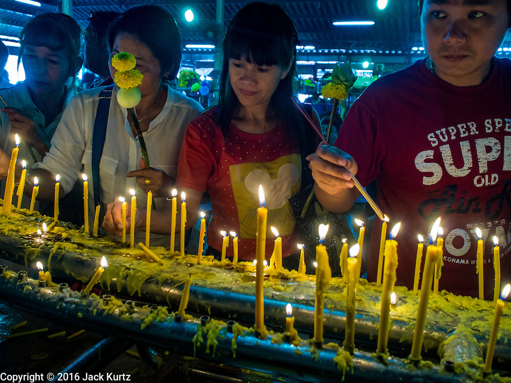 14 JANUARY 2016 - CHACHOENGSAO, CHACHOENGSAO, THAILAND: People light candles while praying at Wat Sothon. Wat Sothon, in Chachoengsao, is one of the largest Buddhist temples in Thailand. Thousands of people come to the temple every day to pray for good luck, they make merit by donating cooked eggs and cash to the temple. The temple dates from the Ayutthaya period (circa 18th century CE).         PHOTO BY JACK KURTZ