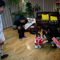 BEIJING, 25. JANUARY, 2009 :   Mr. Li's  grandchild  receives &quot;hongbaos&quot; ( red envelops filled with money ) from relatives on new years' eve  in Beijing .<br /> Mr. Li, a paper factory owner, is facing one of his most difficult times .&quot; Last November the market suddenly went down ,&quot; Li says.   <br /> He had bought paper, a lot of paper, and paid 7000 Yuan/ t .<br />  Li's company buys paper from paper mills and lives from the sales to publishing houses and other companies.  Since the market's collapse , he manages to sell the paper only for 6000 Yuan/t.<br /> His clients' export business to the USA had shrunk in Southern China. Mobile phone manufacturers don't need paper for the instruction guides to their mobile phones anymore as their US clients buys less China- made mobile phones.<br />  Toy manufacturers don't need paper anymore  because Americans import less toys from China. &quot; The crisis has driven many of my clients into bancruptsy&quot;, says Li.<br />  <br /> China's Communist Party  which will celebrate its 60th anniversary in October, currently faces its biggest challenge since the beginning of the economic reforms 30 years ago  : &quot; The phase of  rapid economic growth is over. For the first time the government is threatened with a  mistrust of a wide section of the population&quot;, warns the Communist party's Shang Dewen in Beijing.   <br /> Not only the China's poorest worry about the furture, but as well China's middle class is concerned about the crisis.     1,5 Millionen university graduates didn't find a job until the end of 2008  and this summer there'll be an additional  6,1 Million new graduates. More than 12 percent of university graduates face unemployment in 2009.