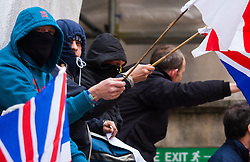 Whitehall, London, April 4th 2015. As PEGIDA UK holds a poorly attended rally on Whitehall, scores of police are called in to contain counter protesters from various London anti-fascist movements. PICTURED: PEGIDA supporters wait for their rally to begin