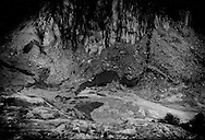 The end of a glacier: The final terminous, or end moraine, for the Fiescher Glacier, the Alps' 3rd longest, progresses up a valley that 100 years ago it filled to a depth of at least 30 m or more.  The sheer, black rock-liked faces free of rubble is the glacial ice just before it melts and washes down the valley to the sea.  Burghutte, Switzerland.