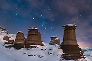 Orion rising behind the iconic Hoodoos on Highway 10 east of Drumheller, Alberta, near East Coulee, on a moonless January night, with illumination by starlight and by a nearby yardlight providing some shadows and warmer illumination. Clouds are beginning to move in and are providing the natural star glows. <br /> <br /> This is a stack of 10 x 10-second exposures for the ground, mean combined to smooth noise, plus one 10-second exposure for the sky to minimize trailing. All at f/2.8 with the 24mm Sigma Art lens and Nikon D750 at ISO 3200. Taken January 10, 2016.