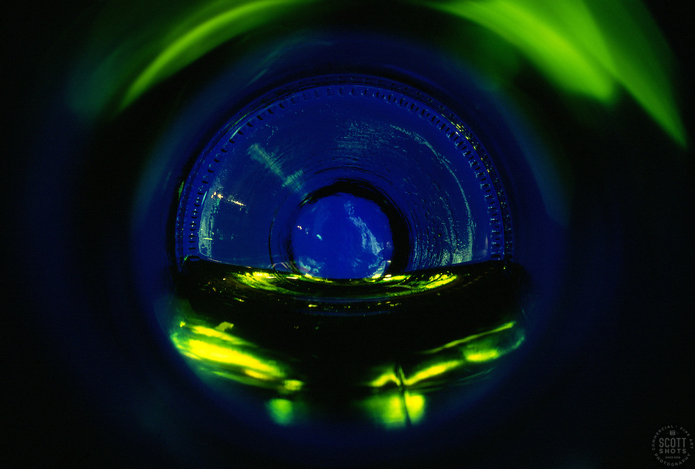 """Beauty at the Bottom: White Wine 2""- This image is a photograph of a wine bottle shot right down the mouth of the bottle. A television provides the main light source."