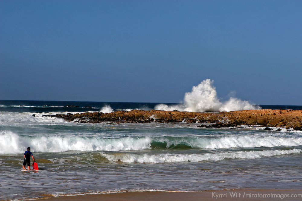 Africa, South Africa, Plettenberg. Body boarder heads into waves at Plettenberg Bay beach.