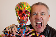 "Damien Hirst Portrait sticks tongue outwith his artwork.""St Elmo's Fire"".2008.Household gloss on plastic skeleton.1700 x 425 x 435 mm.© Damien Hirst. All rights reserved, DACS 2010.Photographed in his Chalford Studio, near Stroud, Gloucestershire"