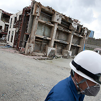 Tsunami devastation in Onagawa, Tohoku region, Japan, on Friday 17th June 2011.Tsunami destruction, caused by the March 11th earthquake and tsunami in Onagawa, Tohoku region, Japan, on Friday 17th June 2011. Workers stand beside a building which lays on it's side, pushed over by the power of the March 11th tsunami, in Onagawa, Tohoku region, Japan, on Friday 17th June 2011.