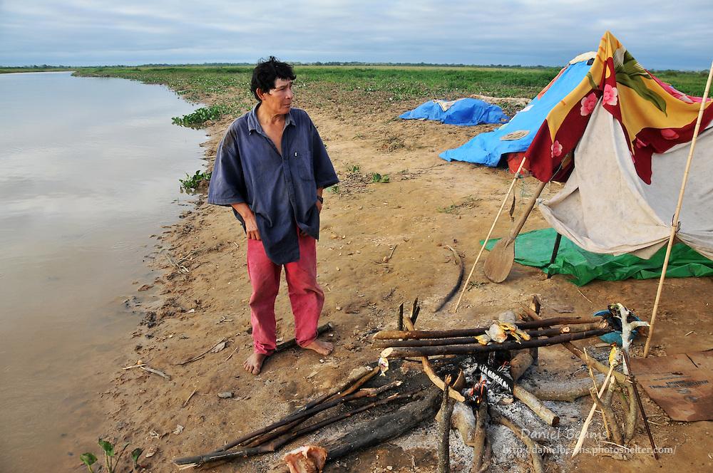 Chimani man cooking dinner on river near San Lorenzo de Moxos, Beni, Bolivia