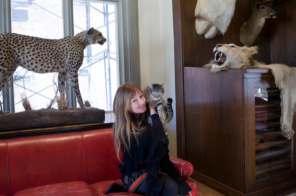 Lorie Karnath, president of The Explorers Club, with the house cat in the Trophy Room of the club, New York City...Founded in New York City in 1904, The Explorers Club promotes the scientific exploration of land, sea, air, and space by supporting research and education in the physical, natural and biological sciences. The Club's members have been responsible for an illustrious series of famous firsts: First to the North Pole, first to the South Pole, first to the summit of Mount Everest, first to the deepest point in the ocean, first to the surface of the moon--all accomplished by our members.