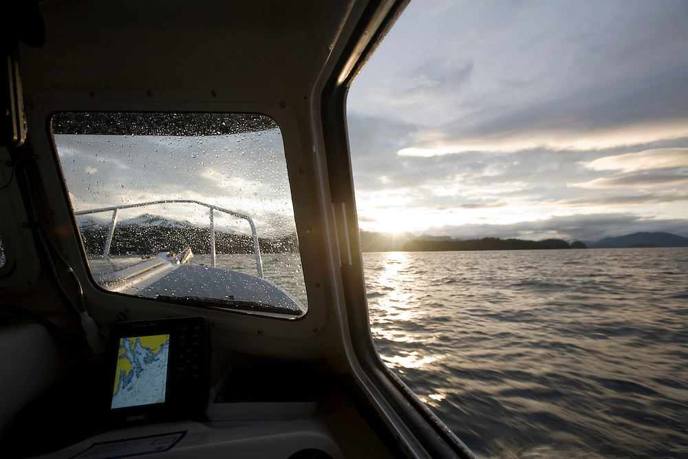 USA, Alaska, View through windows of power boat motoring through Frederick Sound at sunset in windy conditions