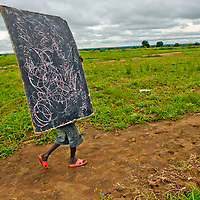 AA young boy carries the class blackboard for an outdoor lesson at a school in the Nimule area of Sudan.