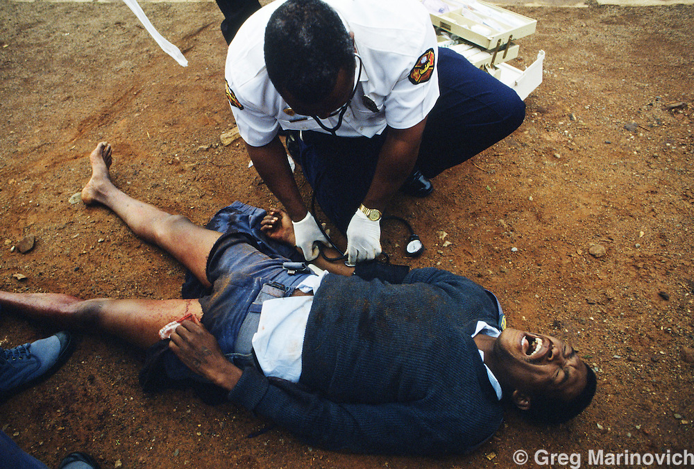 Dube, Soweto, 1994, South Africa:  Medics treat a manwho had been wounded in a train subway in Soweto. 1994.