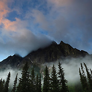 Storm clouds and fog blow past Mount MacDonald, located in Glacier National Park, Canada.