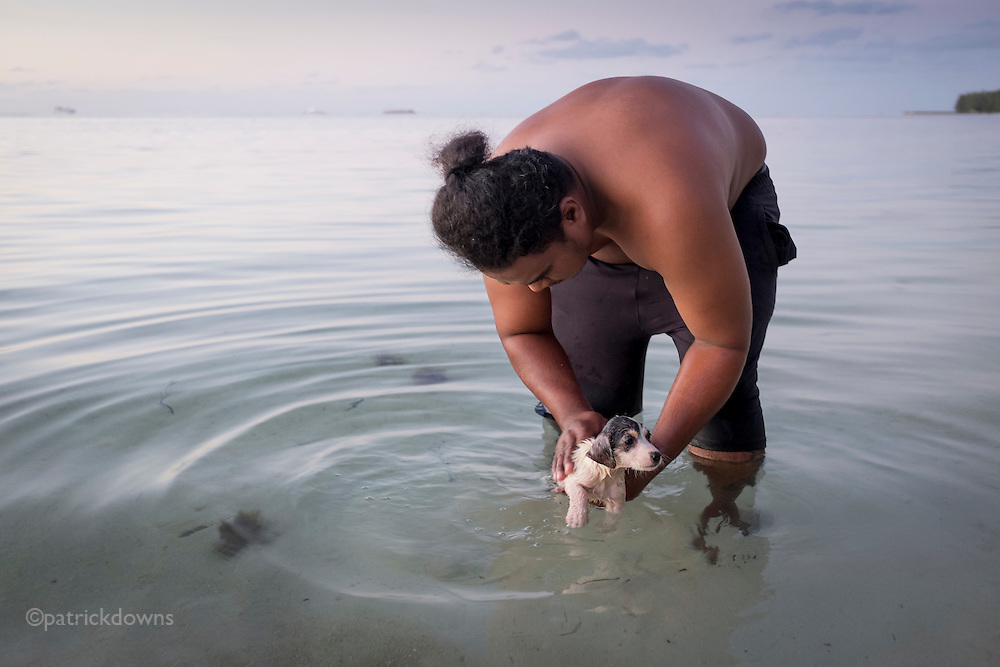 "A local Carolinian man giving his puppy a flea bath in the lagoon on Saipan's west side. Like the Hawaiians use the term ""bra"" or ""bruddah"" to refer to people, the Carolinian term is ""bui bui.""  While people from the Caroline Islands are a minority on Saipan, settling there after typhoons damaged their island, their language is one of the official languages along with Chamorro and English."