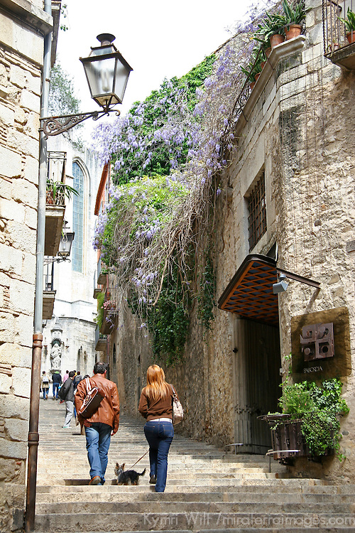 Europe, Spain, Girona. Couple walking dog in Forca Vella street of Girona.
