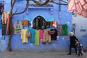 "A girl walks her brother home from school past a display of colorful clothes, offset by the striking blue walls in Chefchaouen, Morocco, whose ""medina"" (old city) is famous for its blue buildings."