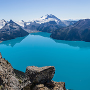 From stunning Panorama Ridge, admire the vibrant turquoise color of Garibaldi Lake, which comes from glacial flour suspended in meltwater from Sphinx and Sentinel Glaciers. Above the lake rise Mount Garibaldi (2678 m or 8786 ft), a potentially active stratovolcano. Garibaldi Provincial Park is east of the Sea to Sky Highway (Route 99) between Squamish and Whistler in the Coast Range, British Columbia, Canada. A hiking loop to Garibaldi Lake via Taylor Meadows Campground is 11 miles (18k) round trip, with 3010 ft (850m) gain. Panorama Ridge is 6 miles (10k) RT with 2066 ft (630m) gain from either Taylor Meadows or Garibaldi Lake Campground (or 17 miles RT with 5100 ft gain from Rubble Creek parking lot). This panorama was stitched from 2 overlapping images.