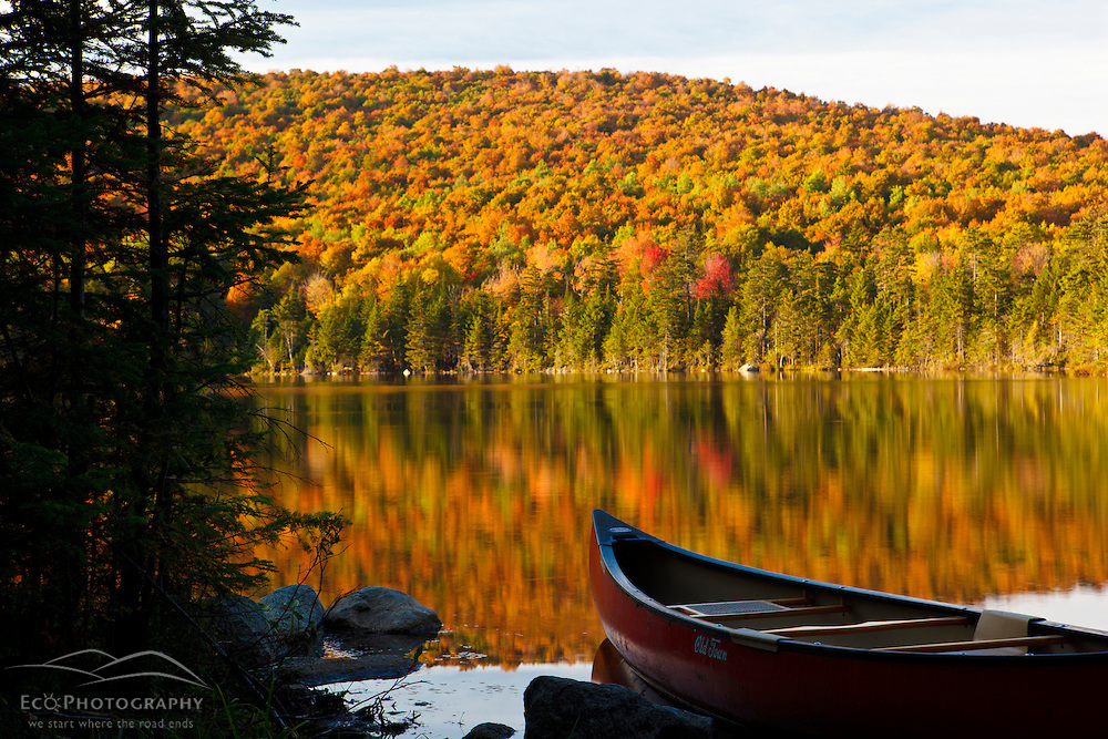 A canoe on the shoreline of Pond of Safety in the Randolph Community Forest. in New Hampshire's White Mountains.