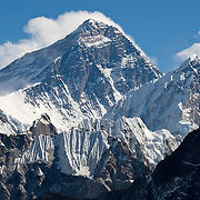 """View from Gokyo Ri: Mount Everest (29,035 feet / 8850 meters elevation above sea level, from 1999 GPS measurement), the highest mountain on Earth, was first called Chomolungma or Qomolangma (""""Goddess Mother of the Earth"""" in Tibetan). In 1865, Andrew Waugh, the British surveyor-general of India named the mountain for his chief and predecessor, Colonel Sir George Everest. In the 1960s, the Government of Nepal named the mountain Sagarmatha, meaning """"Goddess of the Sky"""". The mountain, which is part of the Himalaya range in High Asia, is located on the border between Nepal and Tibet, China. Sagarmatha National Park was created in 1976 and honored as a UNESCO World Heritage Site in 1979."""
