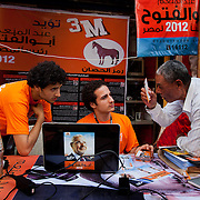 Campaign volunteers for Egyptian Islamist presidential candidate Abdul Moneim Aboul Fotouh help a local voter find his polling center and voter ID number at a roadside campaign table May 17, 2012 in Mansoura Egypt. Grass roots campaigning tables like this are an unfamiliar sight to Egyptians, who are now preparing for their first truly democratic presidential vote in history. (Photo by Scott Nelson)