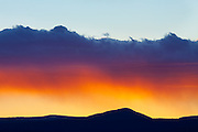Sunset over Petaca Peak west of Taos, New Mexico.