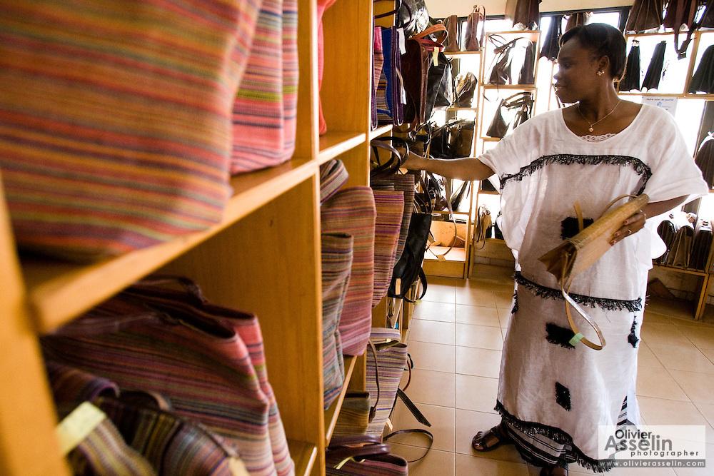 A woman lays bags for sale in the main shop of the Village Artisanal de Ouagadougou, a cooperative that employs dozens of artisans who work in different mediums, in Ouagadougou, Burkina Faso, on Monday November 3, 2008.