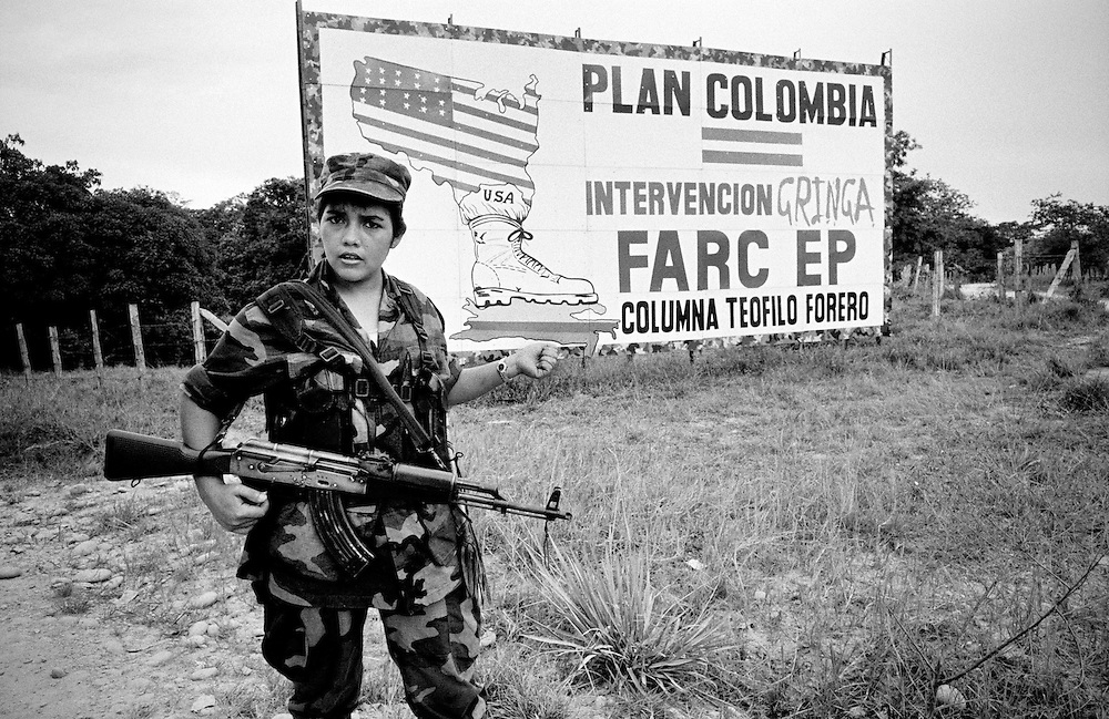 A female FARC fighter at a checkpoint besides a huge billboard critising US intervension in Colombia.<br />