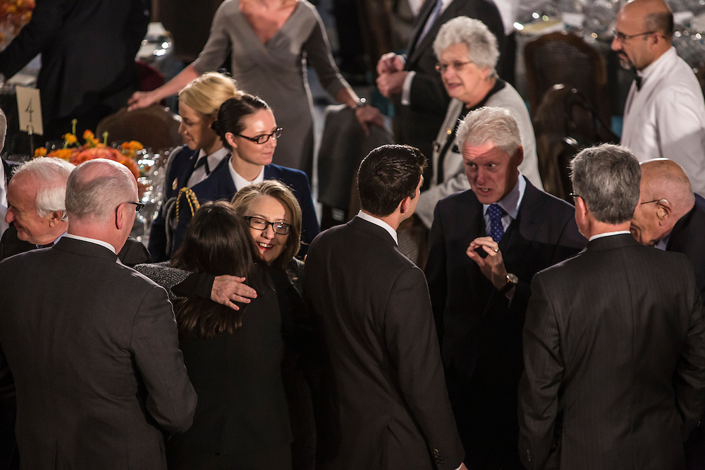 Secretary of State Hillary Clinton gives a hug as former President Bill Clinton talks with Representative and former Republican Vice Presidential candidate Paul Ryan (R-WI) on Monday, January 21, 2013 in Washington, DC.