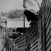 Border jumper plays Peek-a-Boo on wall in San Ysidro, CA.  1993
