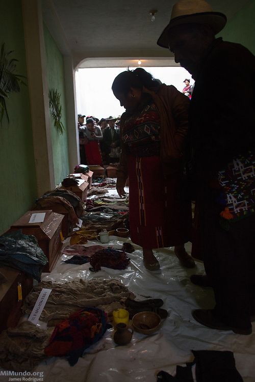 Ixil Mayan residents of Nebaj gather to identify clothing and other belongins exhumed along with the human remains of 36 war victims as these are returned to their surviving family members for a proper burial. Most of the victims, exhumed from mass graves in Xe'xuxcap, near Acul, starved in the mountainside while fleeing State-led repression in 1982. Most of the remains, exhumed by members of the Forensic Anthropology Foundation of Guatemala (FAFG) in 2013, were identified using DNA analysis and buried 35 years after their death. Nebaj, Quiché, Guatemala. February 2, 2017.