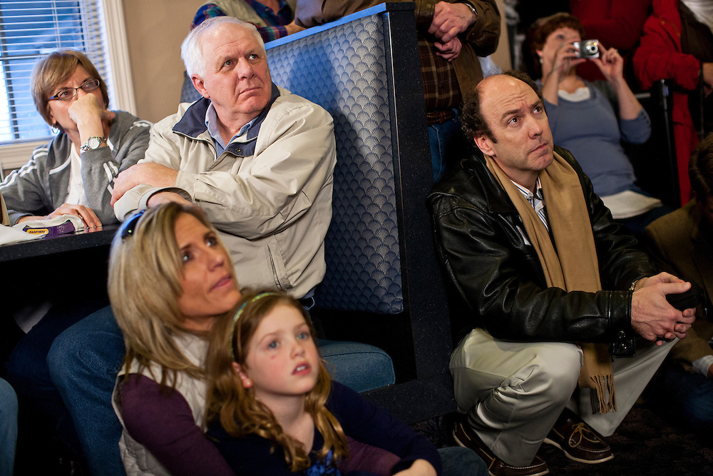 People listen as Republican presidential candidate Mitt Romney meets with voters at the Family Table restaurant on Saturday, December 31, 2011 in Le Mars, IA.