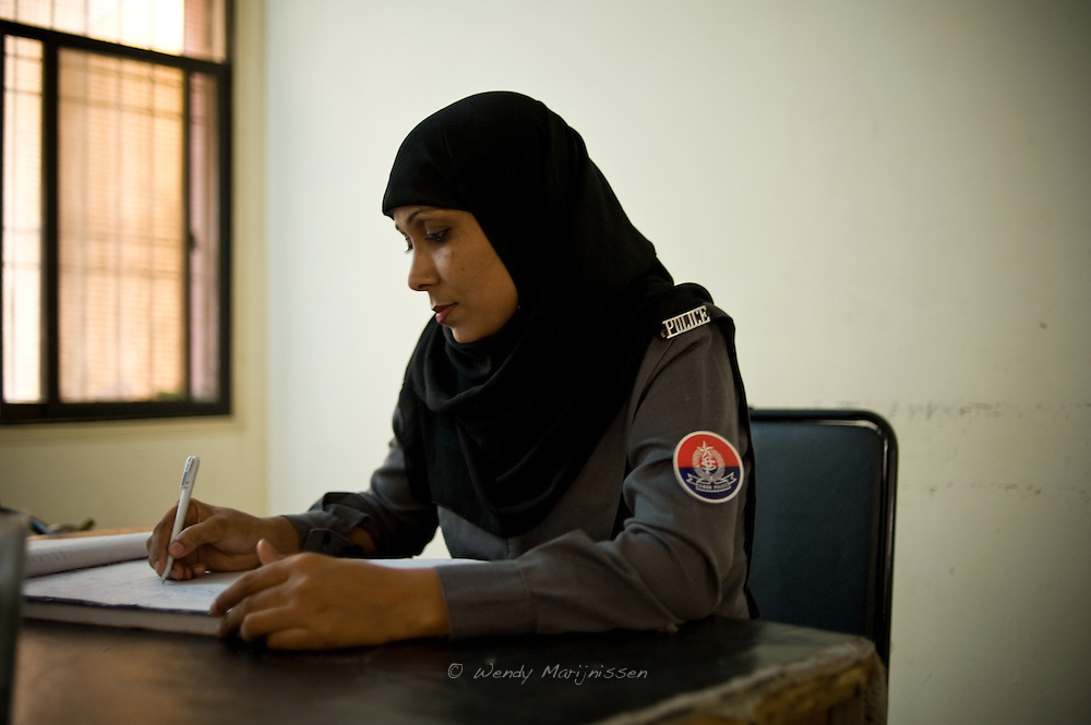 A female police constable writes down the arrival and departure times in a logbook. <br /> Women police officers and constables are often given jobs with no authority and their skills are not being properly used within the police force. Karachi, Pakistan, 2011