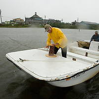 Charlie Harrison (L) stretches line across to the floating docks of a public marina with help of Brian Mattice in Cedar Key, Florda in preparation for Tropical Storm Alberto June 12, 2006. REUTERS/Scott Audette