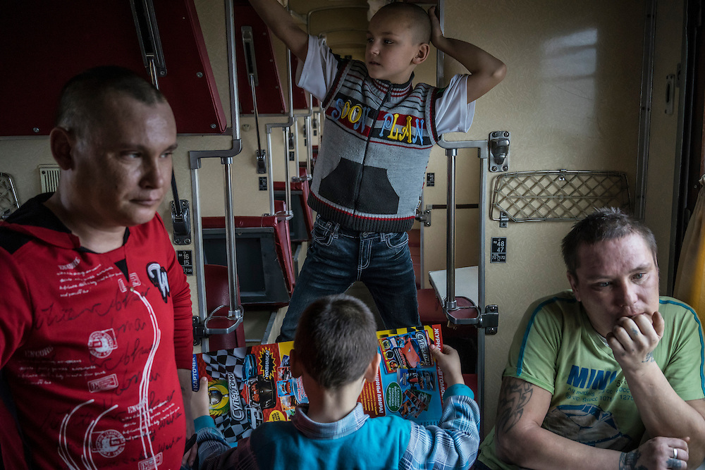 Yevgeny Ryzhkov, 33, Nazar Ryzhkov, 11, Ivan Ryzhkov, 6, and Roman Ryzhkov, 37, from left, who fled fighting in the heavily-contested town of Debaltseve, inside the train car where they are living with other members of their extended family at the train station on Monday, February 9, 2015 in Slovyansk, Ukraine.