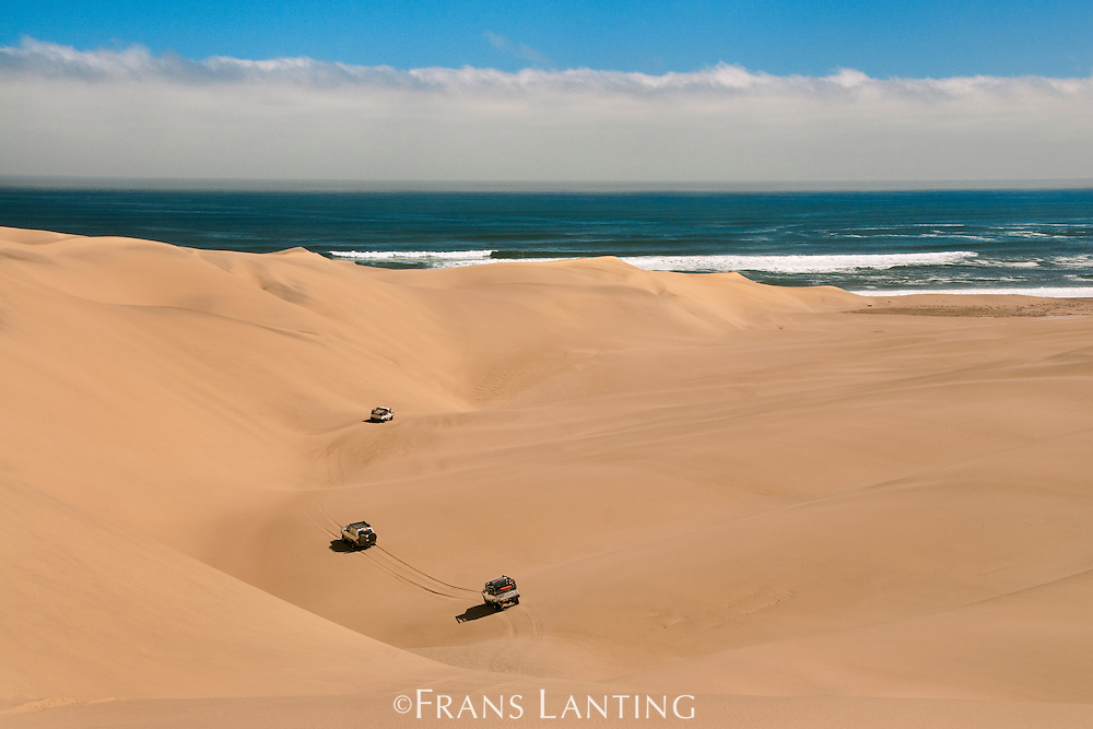 Offroad vehicles crossing sand dunes to Atlantic Ocean, Namib-Naukluft National Park, Namibia