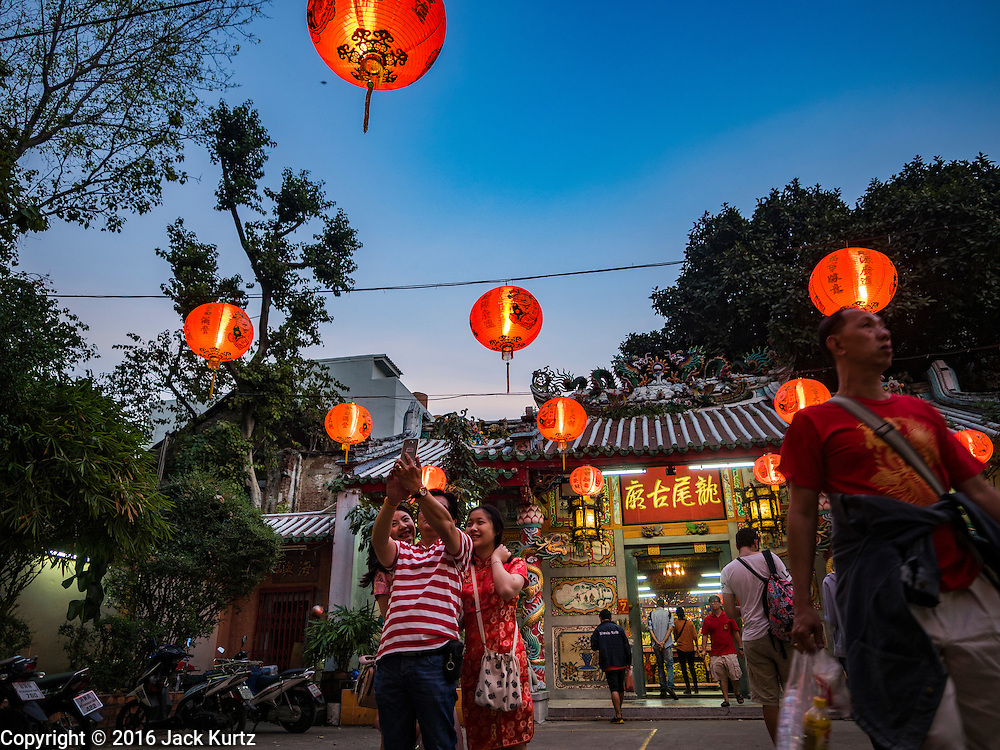 """08 FEBRUARY 2016 - BANGKOK, THAILAND: People take """"selfies"""" in front of a small shrine in Bangkok's Chinatown district during the celebration of the Lunar New Year. Chinese New Year is also called Lunar New Year or Tet (in Vietnamese communities). This year is the """"Year of the Monkey."""" Thailand has the largest overseas Chinese population in the world; about 14 percent of Thais are of Chinese ancestry and some Chinese holidays, especially Chinese New Year, are widely celebrated in Thailand.       PHOTO BY JACK KURTZ"""