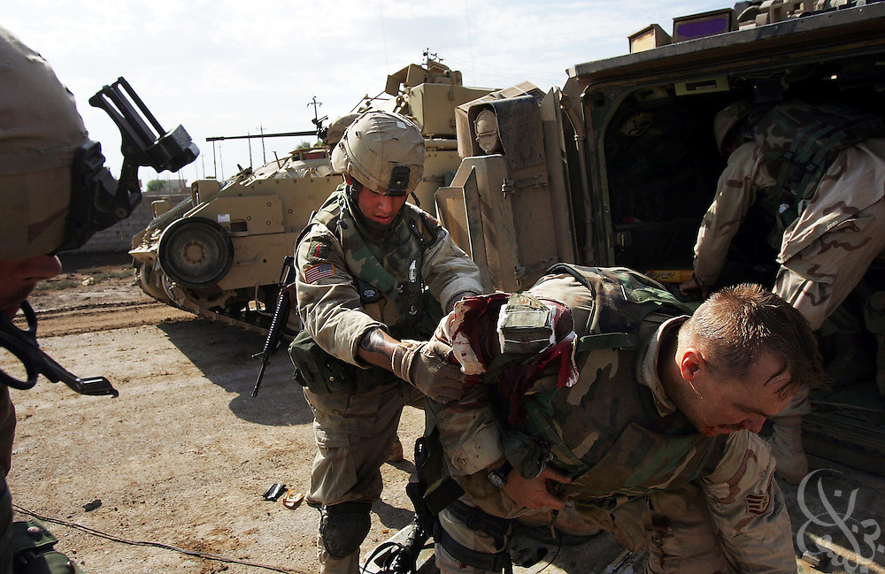 U.S. soldiers treat a wounded Air Force close air support (CAS) controller during a November 13, 2004 sweep of southern neighborhoods in the Iraqi insurgent stronghold of Fallujah.