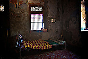 Bed in a front room of an old home. <br />