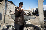 SYRIA - Al Qsair. A Syrian man shows part of the mortar lauched by  Al Assad that destroyed the house behind him, in Al Qsair, on February 9, 2012. ALESSIO ROMENZI