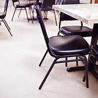 Tables and chairs in a deli-style restaurant.
