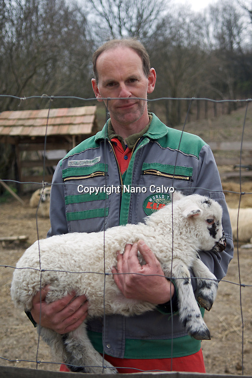 Rancher holding lamb for tourists to see and touch. <br />