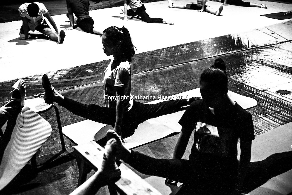 Beijing, Aug.1, 2016 :<br /> a young performer stretches during warming-up excercises for a performance in a theatre in Beijing. <br /> Acrobating performances were recorded for the first time more than 2500 years ago as cheap entertainment for locals in rural China with special shows for the Emperor by the best troupes. While China has seen a dramatic transformation over the years, one component that has not changed is the fact that acrobatic performances are still seen as cheap entertainment, this time though with affluent cities such as Shanghai or Beijing in the background where performers from poor rural backgrounds feel uneasy or as one of my main protagonists from a theatre in Beijing says :&rdquo; We are the underbelly of society. City people look down on us as we are considered old fashioned and penniless.&rdquo;.As seen in the images below,  immense self -imposed discipline, personal sacrifices and rigor,  are necessary to survive daily practises.