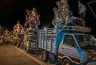 Local village men sit on the roof of a trucks with a large Ganesha statues on the back lined up waiting to have their statues lifted by a crane and immersed in the Bay of Bengal during the Ganesha Chaturthi Festival in Pondicherry, India.