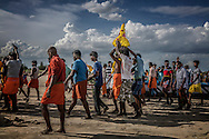 Men carry an idol coated with flowers from the beach back, with two village men deep a trance to the local Hindu trance as part of the Ganesh Chaturthi Festival.  Tiruchchepuram, Tamil Nadu, India.
