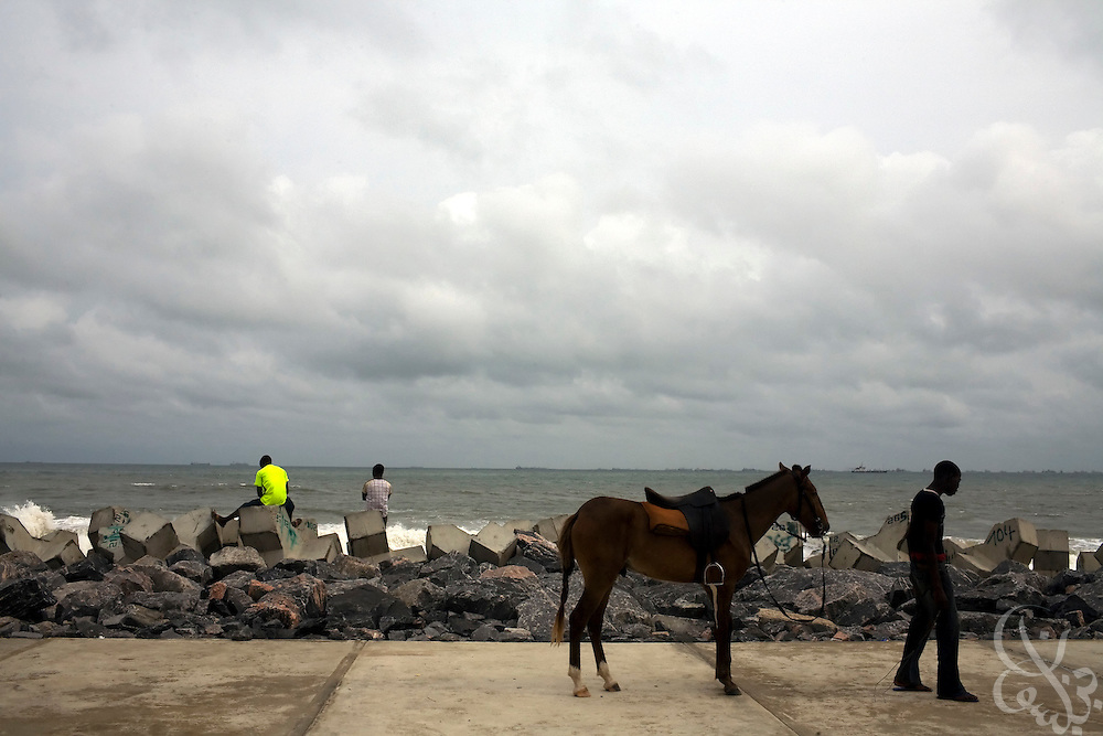 Nigerian teens and a horseman linger along a stretch of beach on Victoria Island July 14, 2008 in Lagos, Nigeria. .