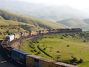 A westbound Union Pacific freight train rounds a big curve in the Tehachapi Mountains of southern California.