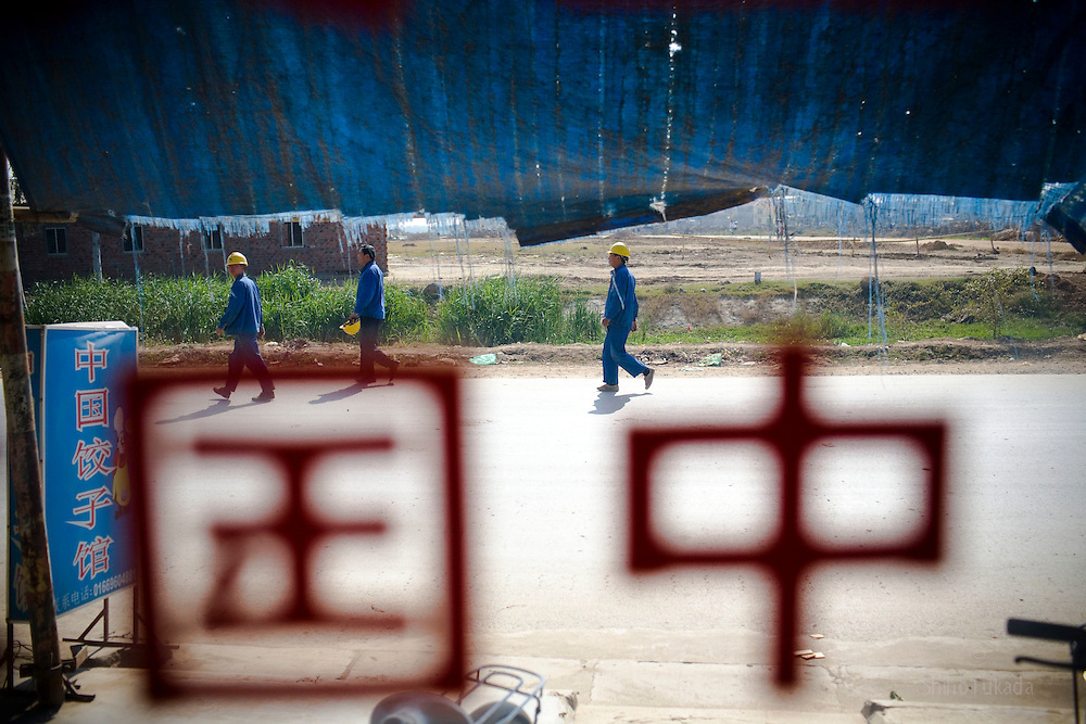 "Workers are seen through a window with ""China"" in Chinese character near the Haiphong Thermal Power Plant construction site in Trung Son, Vietnam, Nov. 22, 2009. At the construction site here, a few miles northeast of the port city of Haiphong, an entire Chinese world has sprung up, including four walled dormitory compounds for the Chinese workers, restaurants with Chinese signs advertising dumplings and fried rice, and currency exchange shops."